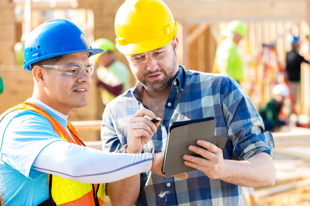 Diverse construction workers or foremen review new home building plans on digital tablet. The men are wearing hard hats and safety glasses.